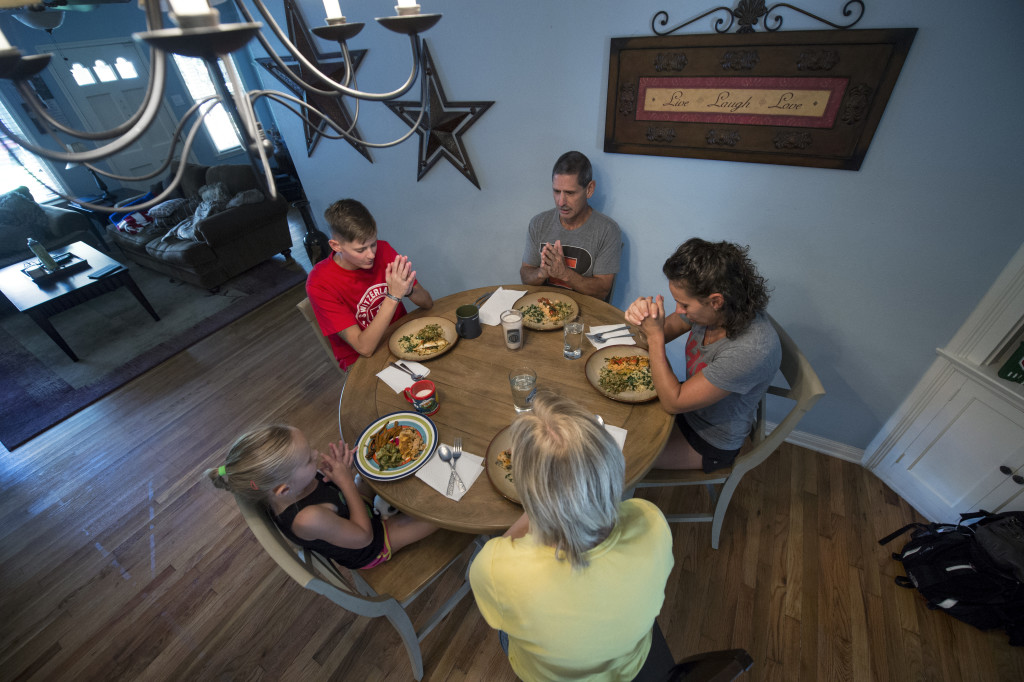 The Elminger family and a best friend pray before dinner at Army Capt. Kelly Elminger's home in San Antonio, Texas June 10, 2015. From right clockwise are Army Capt. Kelly Elminger, mother Berti, daughter and granddaughter Jayden, 9, best friend Aaron Stewart, and father Mark. (DoD News photo by EJ Hersom)